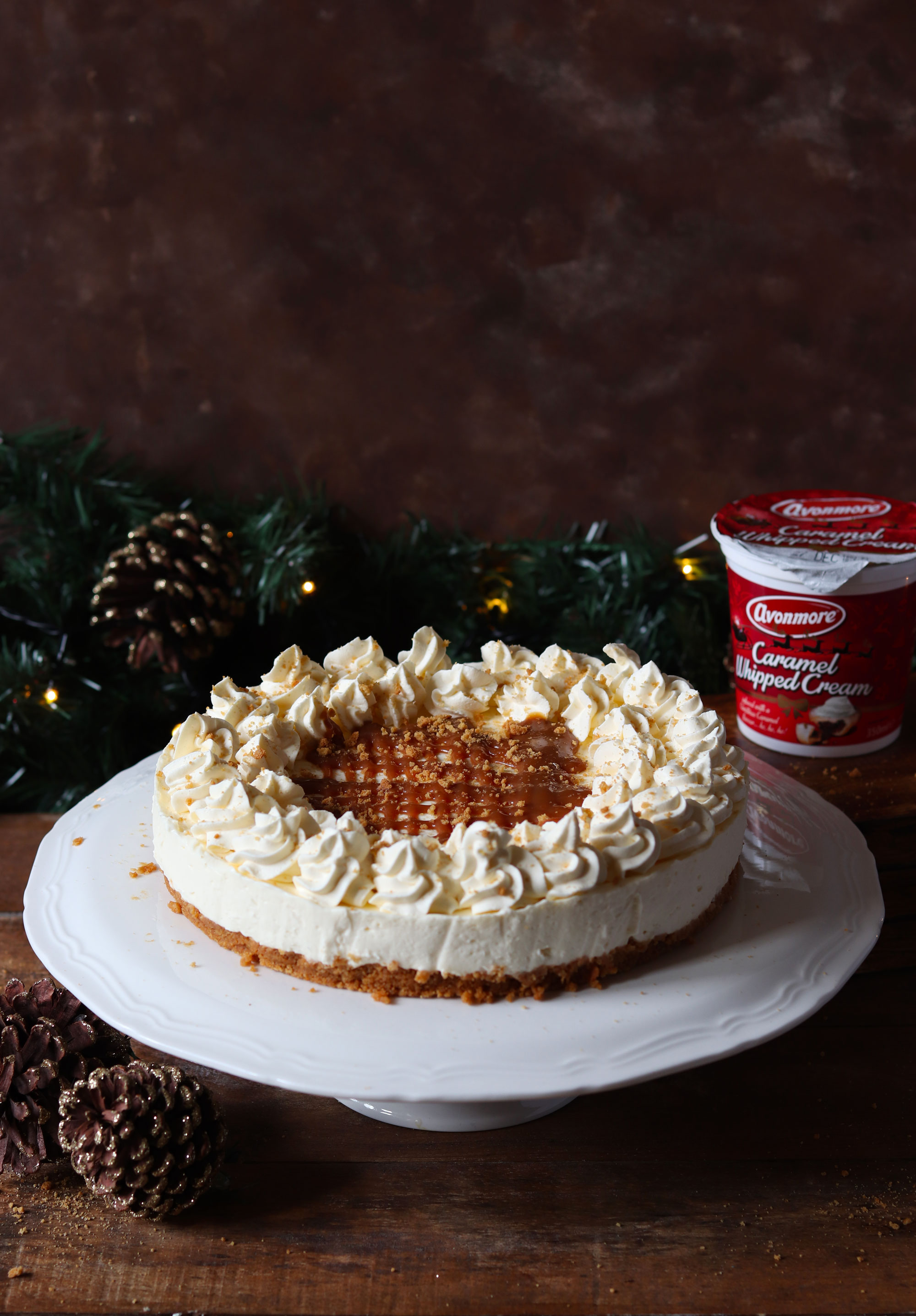 NO BAKE CARAMEL CHEESECAKE WITH A GINGER NUT CRUST AND AVONMORE CARAMEL WHIPPED CREAM FROSTING DRIZZLED WITH CARAMEL SAUCE